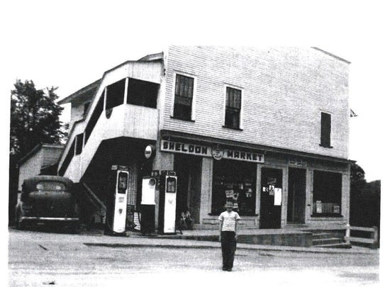 On Jan 25, 1950 Harlow Mower sold the store and property to Clarence and Helen Mercure who ran it as the Sheldon Market. In this 1960 photo, Jim Mercure, their son, stands in front of the store. Clarence skillfully partitioned the second floor as housing for his family.