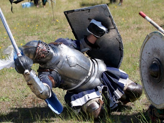 "Sir Martin le Harpur, who goes by the name of Martin Casp, of Issaquah, in modern life, dramatically falls to the ground after being dealt a ""fatal blow"" during a round of the heavy combat tournament at June Faire in Bremerton on Saturday, June 4, 2016. (MEEGAN M. REID / KITSAP SUN)"