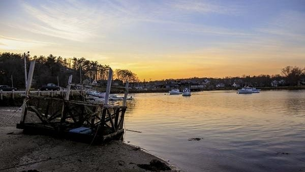 The sun sets over Cohasset Harbor.