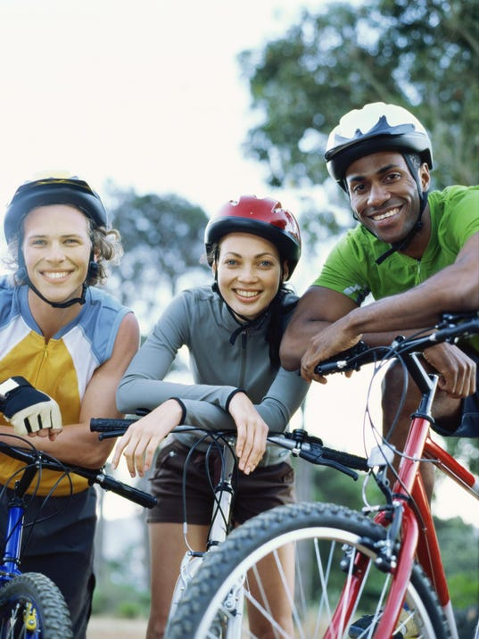 Portrait of two young men and a young woman on mountain bikes