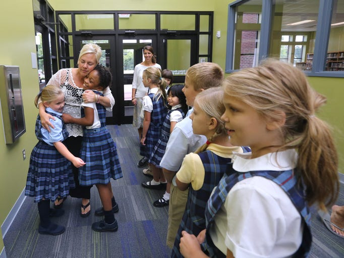 Providence Christian Academy's office staff worker Dawn May hugs her daughter Hannah May, left, and Adora Nwosu, right as Johannah Mackin's 3rd grade class takes a tour of the new areas of the school on the school's first half day on Wednesday July 23, 2014.