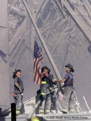 First published in The (Bergen County, N.J.) Record on Sept. 12, 2001, firefighters raise the American flag at Ground Zero on Sept. 11, 2001.