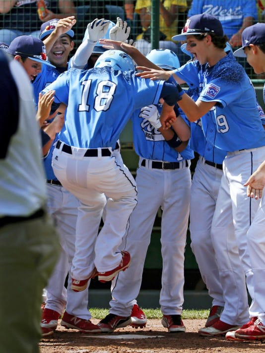 Bonita, California's Nick Maldonado (18) leaps on home plate as he is swarmed by teammates after hitting a grand slam off Bowling Green, Kentucky's Ty Bryant during the third inning of a baseball game in United States pool play at the Little League World Series tournament in South Williamsport, Pa. on Friday. The West won 14-2.