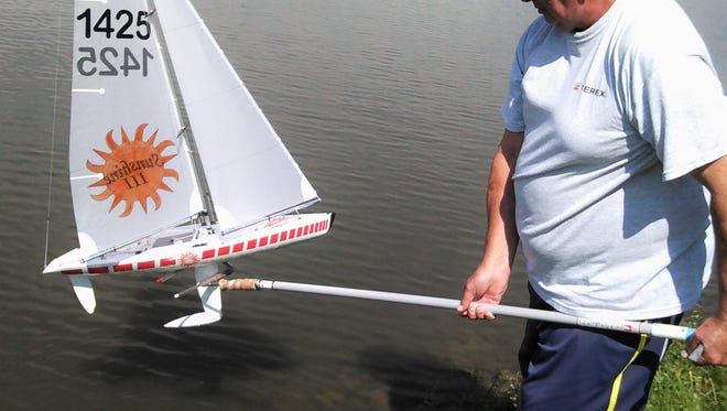 Launching a deep-keeled radio-controlled sailboat from shore is no longer a problem with the contraption demonstrated here by Gregg Metzger of North Liberty.  He attached a telescoping mop handle to a customized paint roller and it works slick.