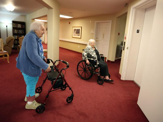 Leona Neubeuger, left, and Fern Gleason wait at the elevator Wednesday, July 22, at Cedar Village Assisted Living & Memory Care in Salem.