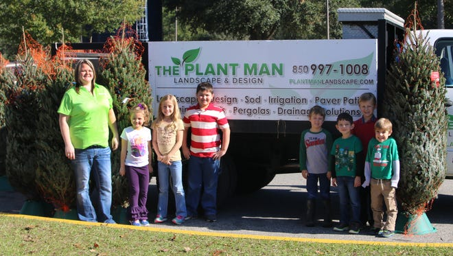Stephanie Waugh from The Plant Man with some of the Fort Braden Elementary School students who received free Christmas trees.