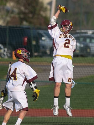 Madison's Pat Grahling (14) and Vince Sapio (2) celebrate their 8-7 overtime win over Morristown in the first round of the Morris County Tournament on Monday.
