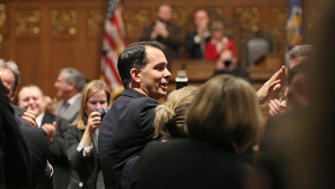 Wisconsin Gov. Scott Walker greets people as he enters the assembly chamber before giving his State of the State address at the state Capitol in Madison, Wis., Tuesday, Jan. 19, 2016.
