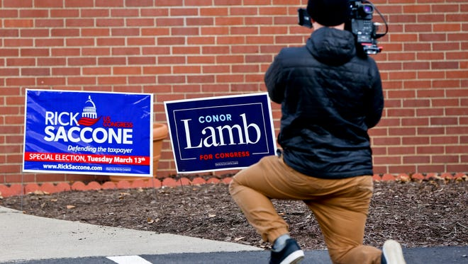 A cameraman takes footage of the signs for the two candidates outside a polling place in the special election being held for the PA 18th Congressional District vacated by Republican Tim Murphy, Tuesday, March 13, 2018, in McKeesport, Pa. Republican Rick Saccone had just voted at the site. Saccone is running against Democrat Conor Lamb.