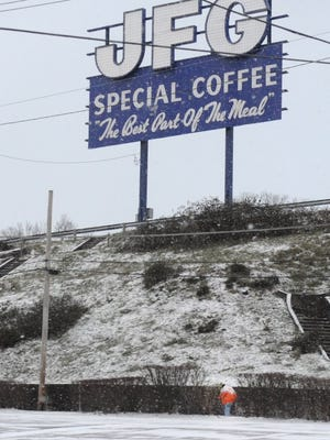A pedestrian walks up Sevier Avenue beneath the JFG Coffee sign on Saturday following overnight snowfall in Knoxville.