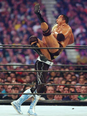 Hulk Hogan takes on The Rock (right) during Wrestlemania X8 in Toronto in this 2002 file photo.