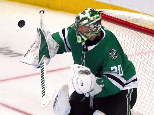 Dallas Stars goaltender Ben Bishop (30) deflects a shot by the Minnesota Wild in the third period of an NHL hockey game Saturday, April 6, 2019, in Dallas. (AP Photo/Richard W. Rodriguez)