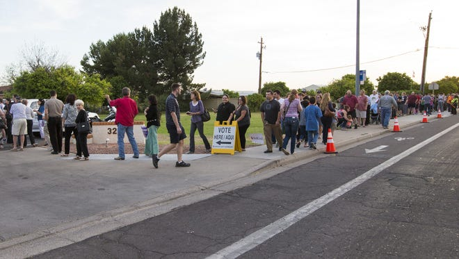 Voters wait in line to cast their ballots at Pilgrim Evangelical Lutheran Church in Mesa.
