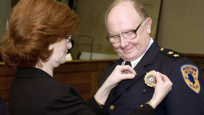 In this file photo, Joanne Oches places a badge on her husband Robert's uniform after he was appointed, and sworn in as the new Middletown Twp. Police Chief Saturday, March 26 2005.
