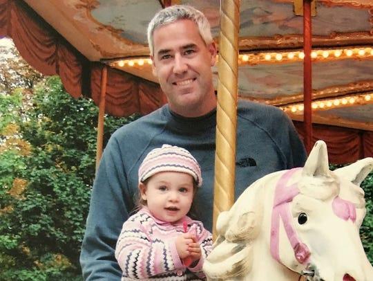 Greg Shamus holds his daughter, Julia, 18 months, on