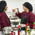 ALEX SLITZ / THE GLEANER Henderson County High School Junior Chef Team members Fernanda Gomez, 17, (left) and Siara Marquez, 17, both of Henderson, work to prepare their signature dish, baked honey garlic chicken with steamed rice and broccoli, at the Thelma B. Johnson Early Learning Center in Henderson, Monday, June 20, 2016. The team will compete in the Kentucky State Fair Junior Chef competition on August 24.