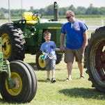 ALEX SLITZ / THE GLEANER Beckett Lear, 5, looks through parked tractors with his father, Jeremy Lear, both of Henderson, during the Shake Rattle and Roll Tractor Drive at the Henderson County Fairgrounds in Henderson, Sunday, June 26, 2016. Proceeds from the event benefit Relay for Life.