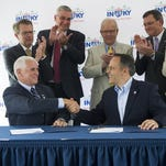 ALEX SLITZ / COURIER & PRESS Indiana Gov. Mike Pence, (left) and Kentucky Gov. Matt Bevin shake hands after signing a Memorandum of Agreement to begin the I-69 Ohio River Crossing Project at Ellis Park in Henderson, Thursday, June 30, 2016.