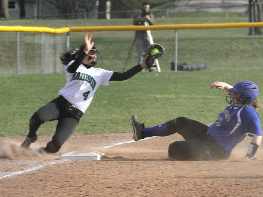 Madison's Sloan Kiser catches the ball as Ontario's Laney Grimwood slides into third base.