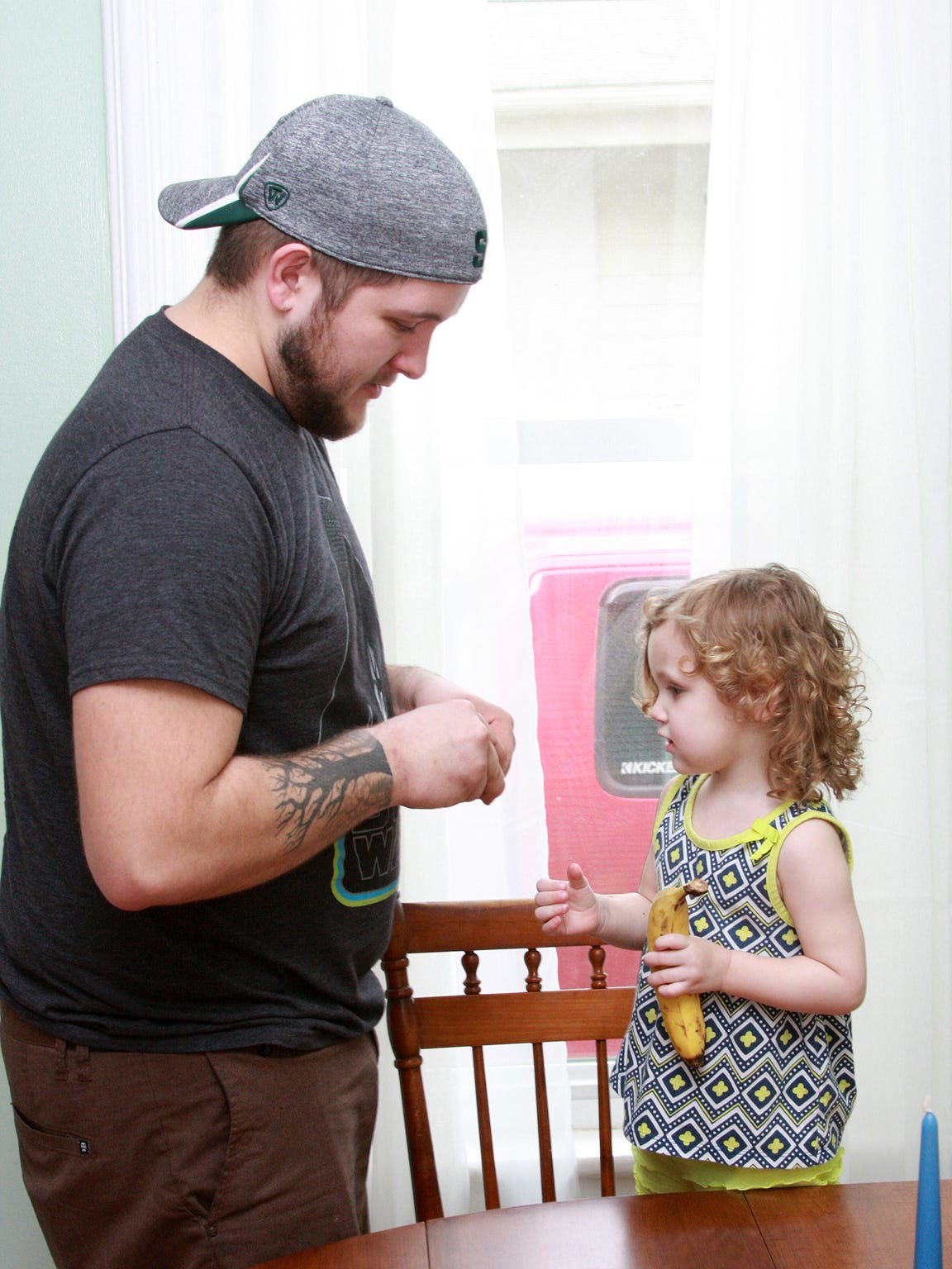 Shawn Bryant, 26, peels a clementine for his 2-year-old