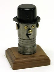 """Small metal caricature of Winston L. S. Churchill mounted on a wood base.  His head and neck are made from an artillery shell with rings at the neck,  At the top is a black metal hat, and the face is made of various metal with a cigar sticking out.  Mounted to a wooden base and written in pencil along the edge, """"Dr. Bernie Cooper  Steve Jancer."""""""