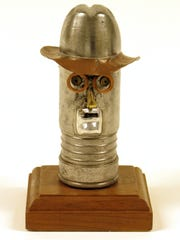 Small metal caricature of Franklin D. Roosevelt mounted