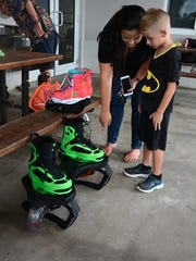 Amber Alvarez of Naples shows the flyboard boots to her son Landon, 6.