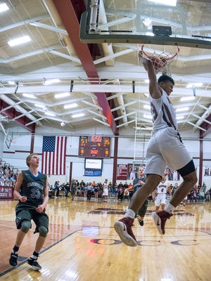 Newark's B.J. Duling throws down a fourth-quarter dunk as Zanesville's Anthony Williams watches Saturday in Jimmy Allen Gymnasium.