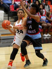 Burkburnett's Paradize Jackson dribbles around Hirschi's Briana Calloway en route to the basket Tuesday evening.