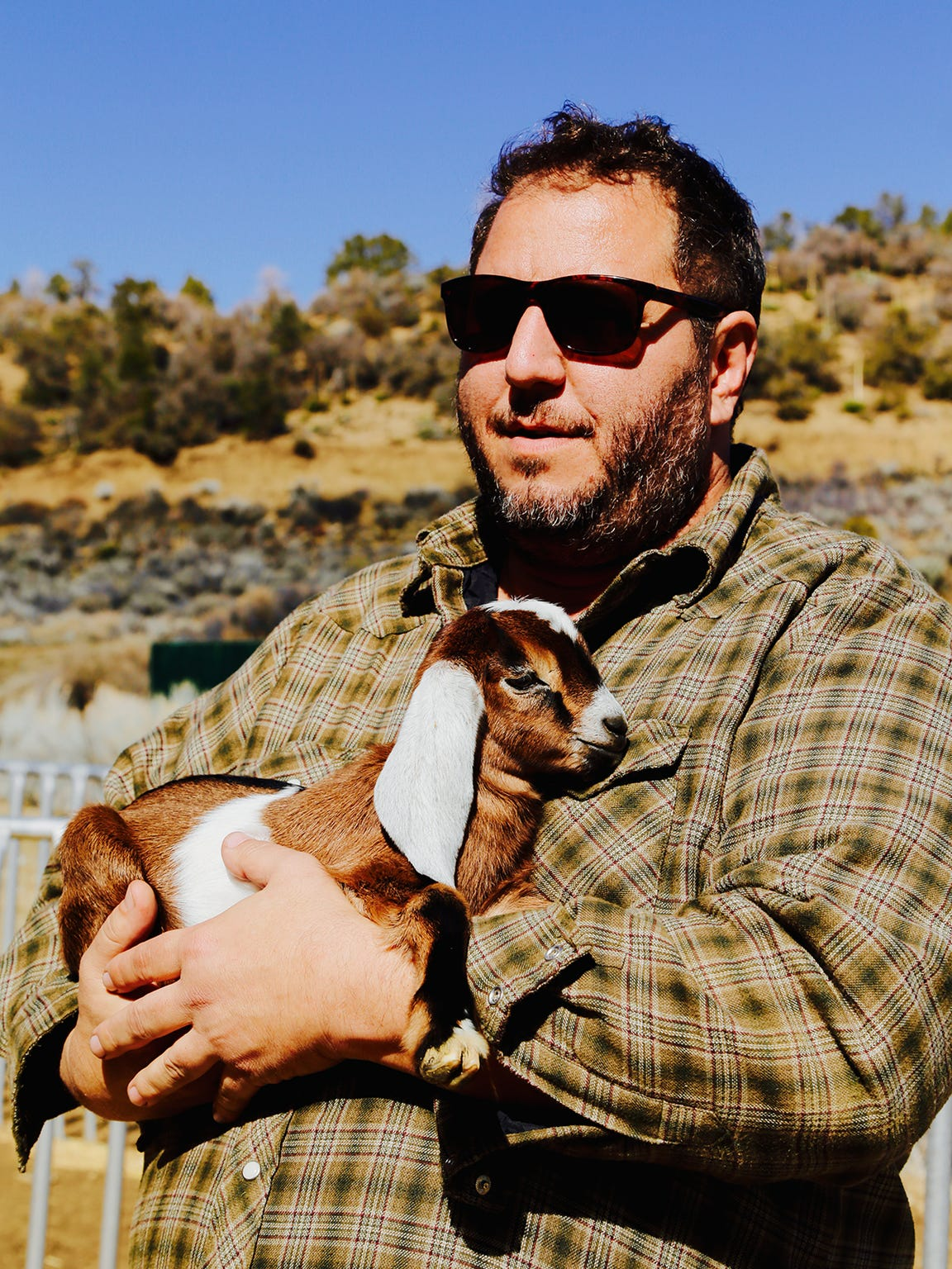 Rick Marino holds a baby goat at Angeles Crest Creamery.