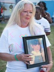 Robin Buonodono, holds a photo of her child, Nicole VanNoty Saturday, Aug. 12.