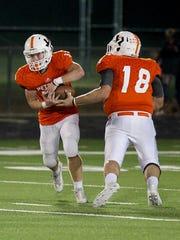 Petrolia quarterback Macon Armour (18) hands the ball