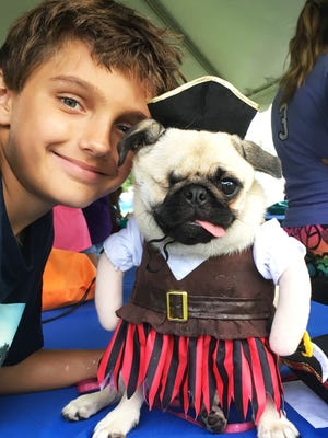 """Ryan Veach with Cocoa, the one-eyed wonder pug, won """"Best Overall"""" in the costume contest at the  Humane Society of the Treasure Coast's Mutt March 5K & Festival on Oct. 14."""