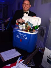 Event committee member Neil Snyder with the cooler of booze, plus an electric guitar, he won in the silent auction. The American Cancer Society's Imagination Ball, Saturday night at the Marriott hotel, raised hundreds of thousands of dollars for the fight against cancer. Lance Shearer/Eagle Correspondent