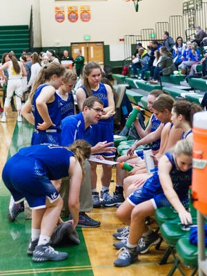 Harper Creek Coach, Phil Hicks, talks to the team during a time out Saturday afternoon against Pennfield
