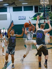 Pennfield Senior, Grant Petersen, goes up for a shot against Harper Creek Saturday afternoon