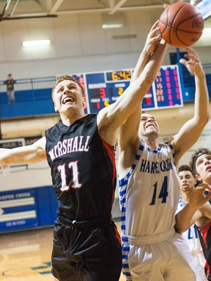 Marshall Junior, Jeremy Luciani, and Harper Creek Senior, Jon Taylor battle for a rebound Friday evening