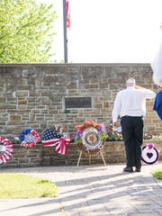 A veteran holds salute after placing the purple heart wreath Monday morning in Marshall.