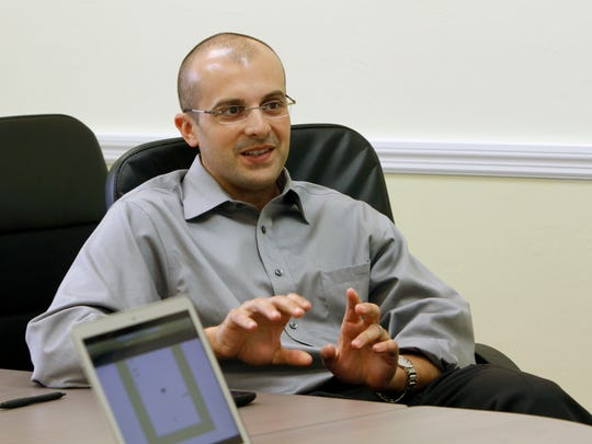 Golf Life Navigators President Jason Becker strategizes with colleagues Thursday, December 17 at their Naples office.