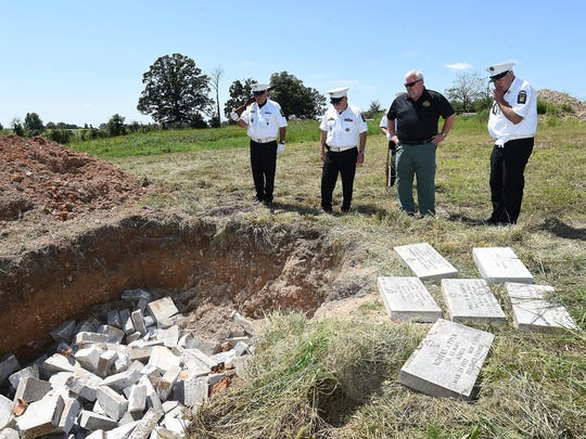 Ozark County Sheriff Darrin Reed, third from left, and members of the West Plains Veterans Honor Guard look over a pit where military headstones were buried Tuesday. The headstones were discovered recently at a Howards Ridge residence in southern Missouri where they were used for a patio and walkway. The discovery caused a national outcry.