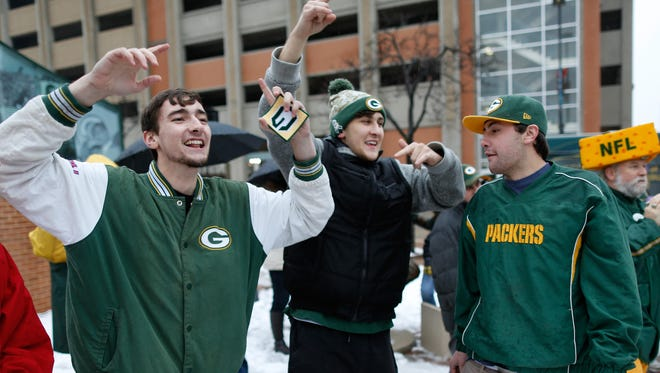 Bobby Blahnik (left) and Jack Charles cheer during a pep rally for the Packers at the corner of Washington and Cherry Streets in Green Bay.
