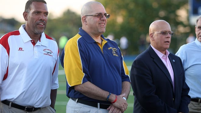 Former Colonia High School football coach Ben LaSala, center, stands with fellow inductees of the NJ High School Football Coaches Association Hall Fame during a halftime ceremony at the Phil Simms North-South Football Classic, Monday, June 29, 2015, at Kean University in Union, NJ.