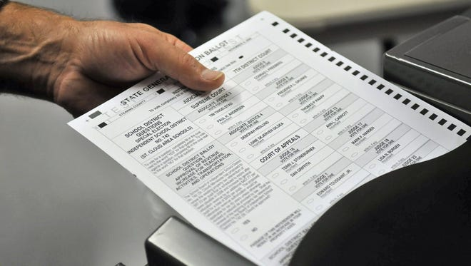 A test ballot is loaded into a voting machine in St. Cloud.