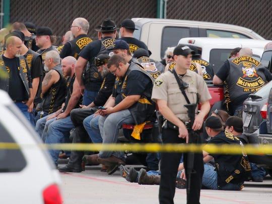 A McLennan County deputy stands guard near a group