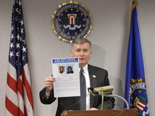 FBI El Paso Special Agent in Charge Douglas Lindquist holds up a poster featuring  FBI most wanted fugitive Terry A.D. Strickland,, who was arrested Sunday in El Paso.