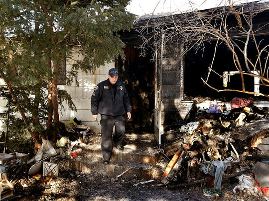 Blue Grass Police Sgt. Garrett Jahns examines a home on East Salem Street Monday, Dec. 25, 2017, where four people died in a fire in Blue Grass, Iowa. Jahns said Tuesday that he couldn't release any of the victims' names or ages yet but that the four were related.