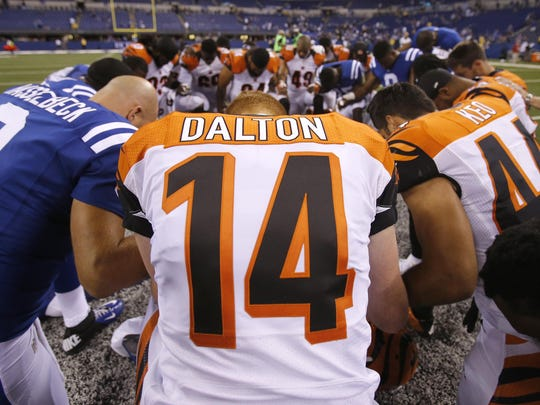 Andy Dalton kneels down in a joint prayer circle after the preseason game between the Bengals and the Indianapolis Colts on Sept. 3, 2015.