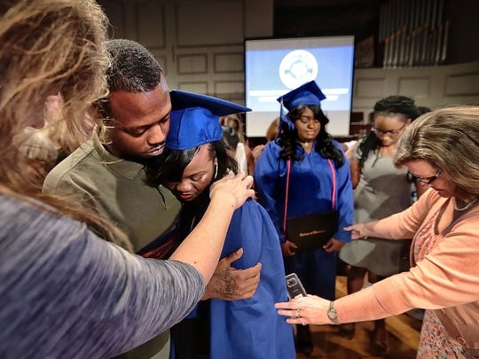 The first graduating class of Brinkley Heights Urban Academy, Chassatea Stone-Bailey (left) and Megan Evans (center) pray with family, fellow students, and members of the faculty during their commencement ceremony at Second Baptist Church Saturday evening. Brinkley Heights is a private Christian school started in 2004 after mass shooting in the neighborhood to help disadvantaged children and youth.