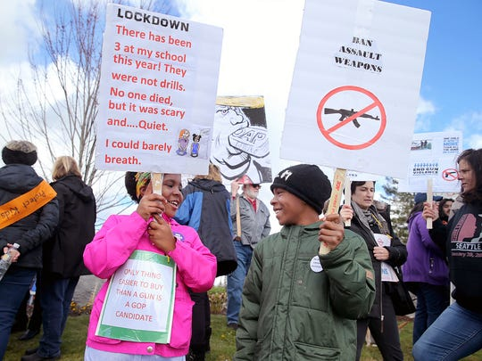 """Aiyanna Clark, 10, and her brother Amare, 12, from Bainbridge Island, hold signs at the Silverdale """"March For Our Lives """" protest Satruday."""