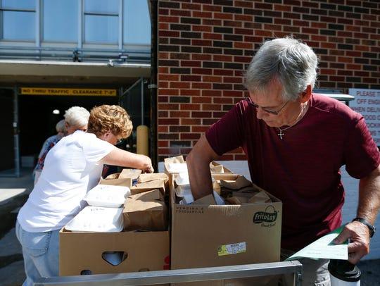 Meals on Wheels volunteer Joe Bob Fuller checks a box
